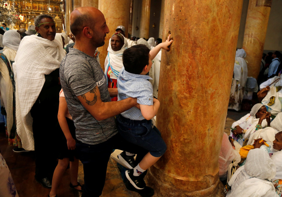 A boy is carried as he places his fingers inside holes in a column that form the shape of a cross at