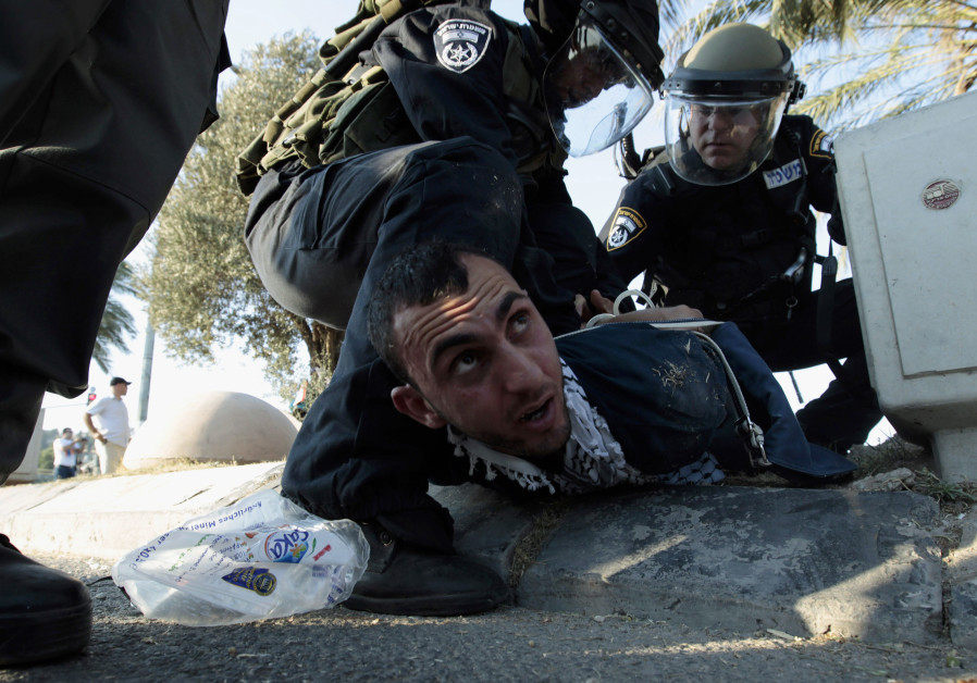 Israeli policemen detain a protester during clashes in the Israeli-Arab town of Umm el-Fahm