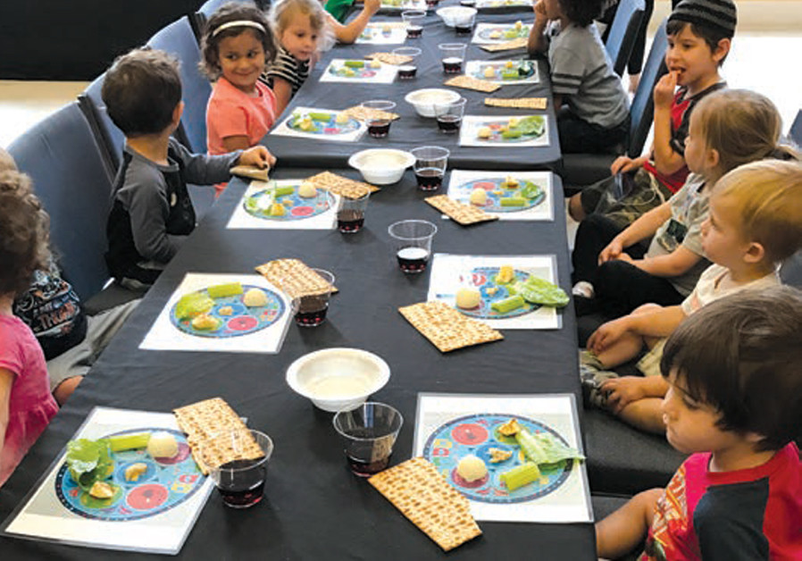 CHILDREN TAKE part in a Passover Seder (CREDIT: ROK FAMILY SHUL)