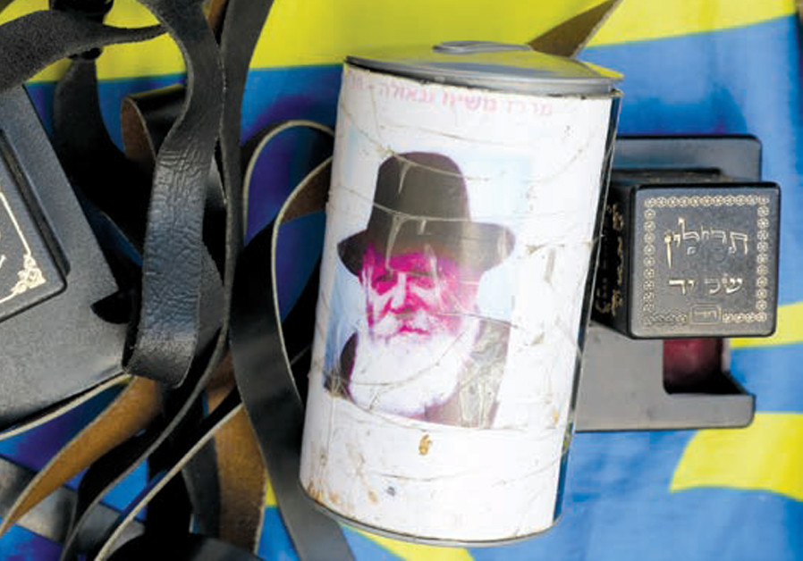 HELPING FELLOW Jews lay tefillin and give tzedaka is a Chabad cornerstone (CREDIT: MARC ISRAEL SELLEM)