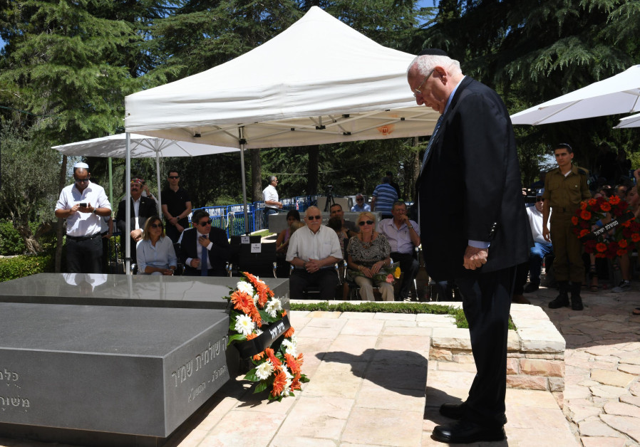 President Reuven Rivlin stands before the graves of Yitzhak and Shulamit Shamir.