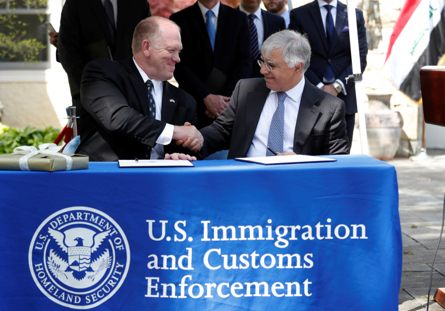 U.S. Immigration and Customs Enforcement Deputy Director Thomas Homan (L) shakes hands with Iraqi Am