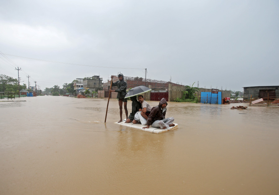 Villagers use a makeshift raft to cross a flooded area on the outskirts of Agartala, India July 15,