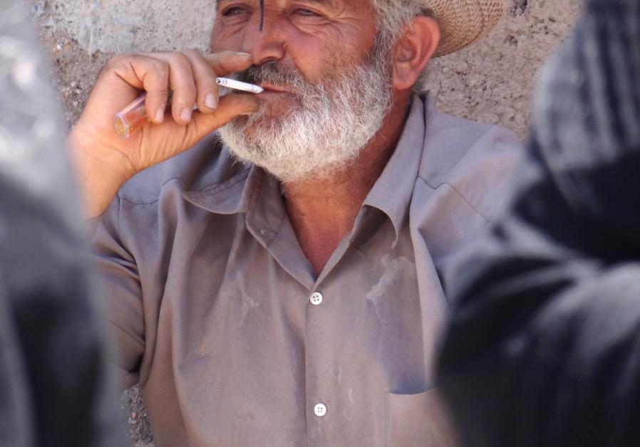 Vendor smokes cigarette in Russian Bazaar - Jolfa - Iranian Azerbaijan - Iran