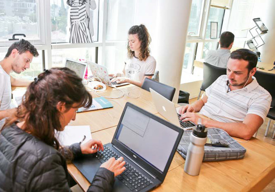YOUNG PROFESSIONALS at work in the Nefesh B'Nefesh Tel Aviv Hub, a free co-working space for olim in the heart of the city. (Credit: YONIT SCHILLER)