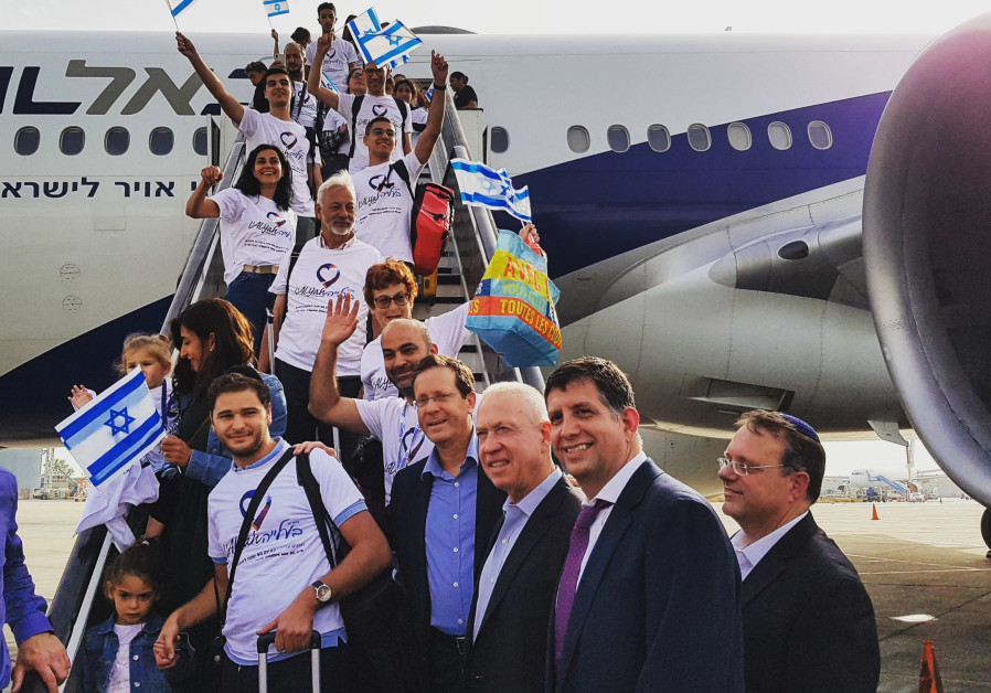 Isaac Herzog poses with French immigrants as they disembark from their aliya flight.