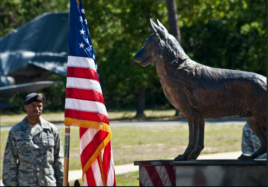 A security forces Airman stands with his military working dog behind the MWD memorial monument durin