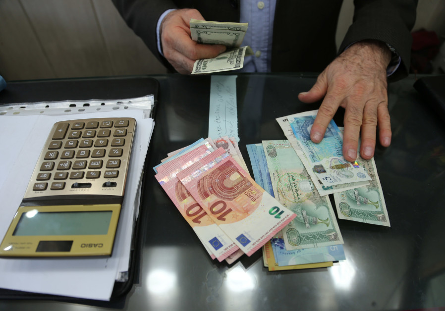 Money changer holds U.S. dollar banknotes as he counts other currency banknotes in Tehran