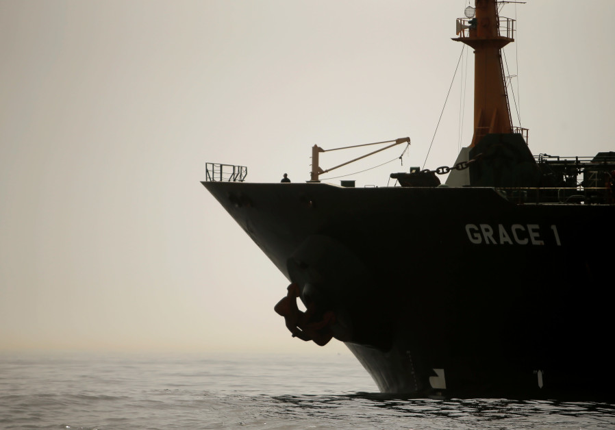 A crew member of the Iranian oil tanker Grace 1 is seen on the bow as it sits anchored after it was