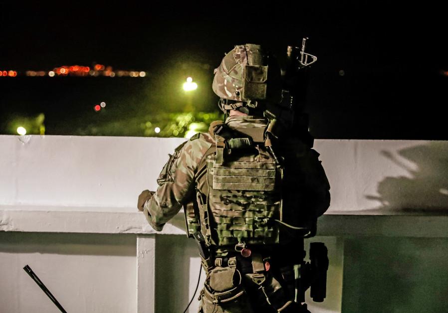 Un soldado británico observa durante una operación que involucra al gran depósito de petróleo Grace 1, que está en suspenso.