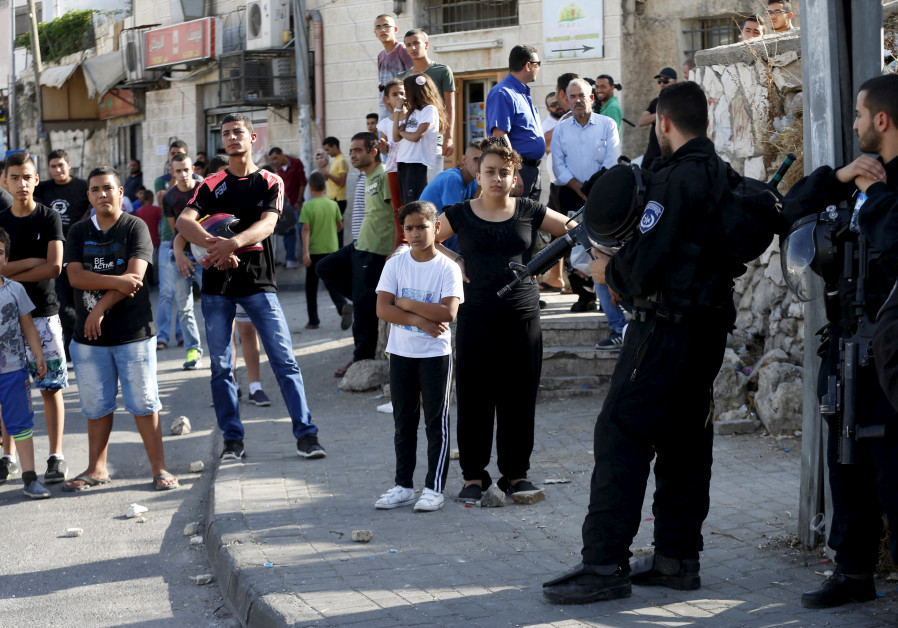 Palestinians look on as Israeli police set up a checkpoint in the Arab east Jerusalem neighbourhood