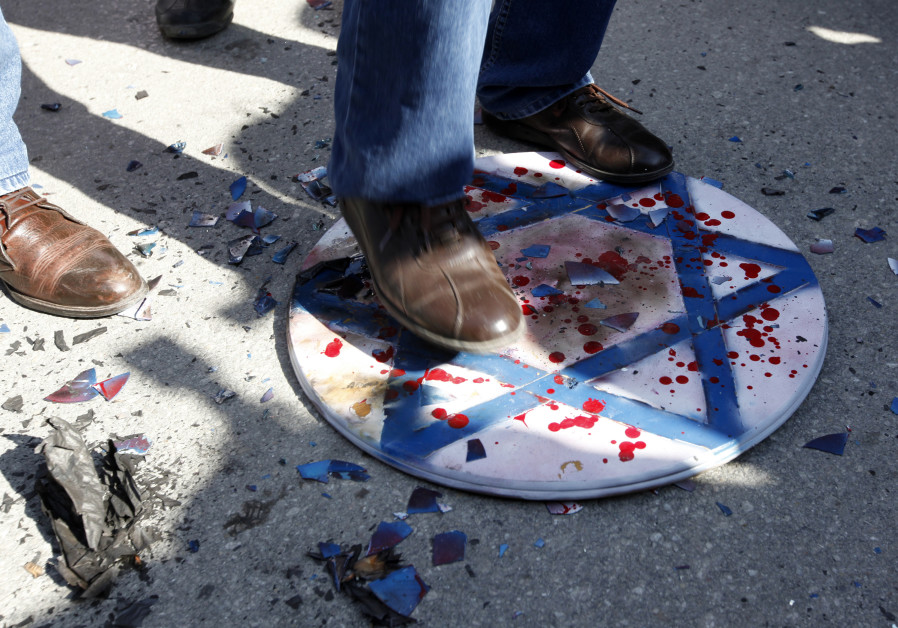 Demonstrators step on a Star of David during a protest against Israel