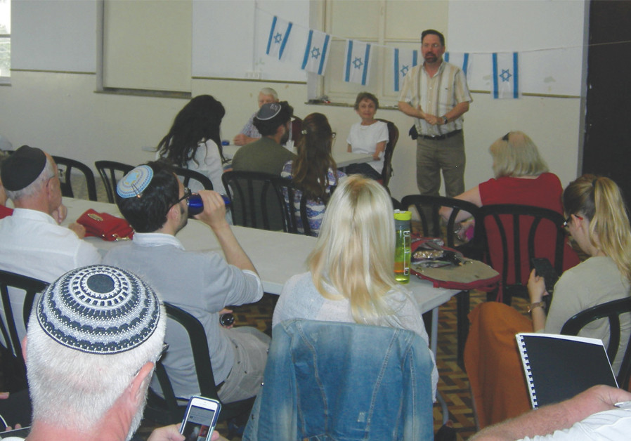THE WRITER (standing) speaks at a Holocaust Remembrance Day program at the Tel Avi International Synagogue. (Credit: RAPHAEL SHUCHAT)