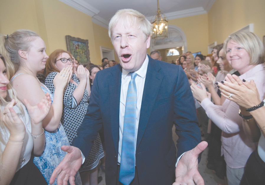 BRITAIN'S PRIME MINISTER Boris Johnson is welcomed in 10 Downing Street by staff on Wednesday.