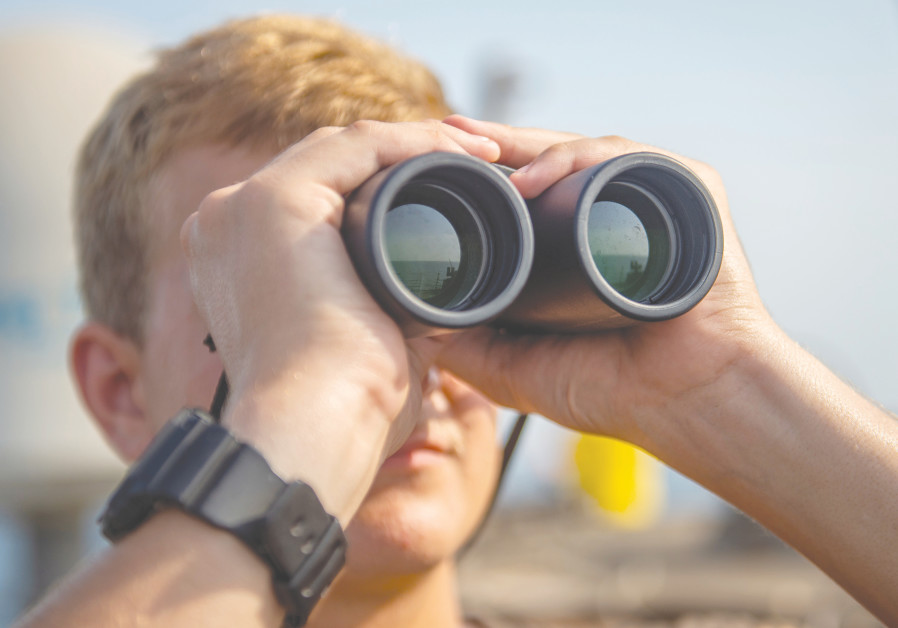 A US SEAMAN scans the horizon during his watch aboard the US Navy Arleigh Burke-class guided-missile