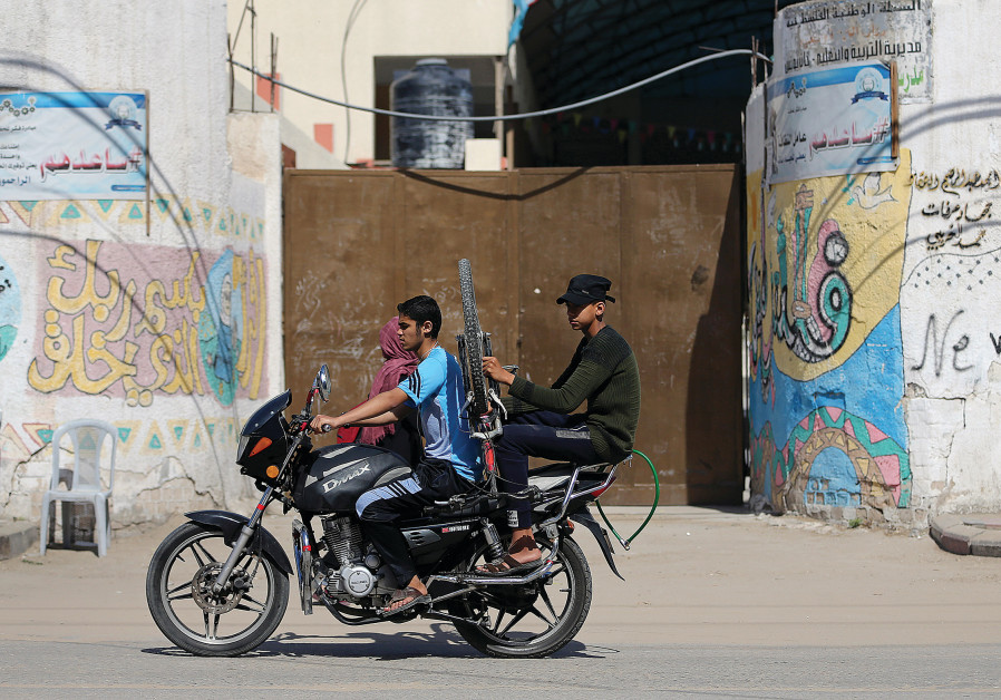 Youths ride a motorcycle past a closed school in the southern Gaza Strip in May.