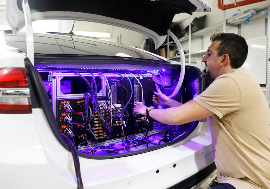 A worker tends to systems in the back of a Mobileye autonomous driving test vehicle, at the Mobileye