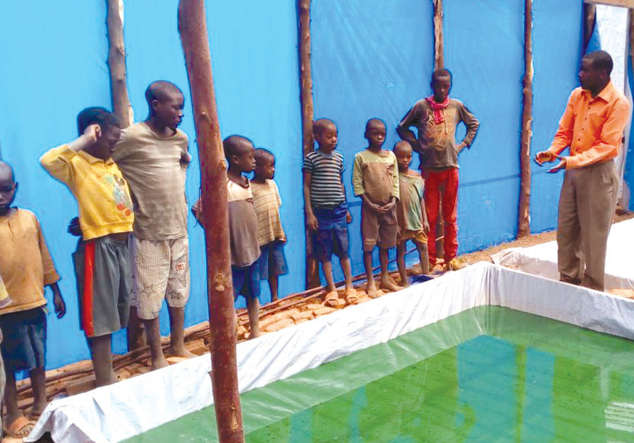 LOCAL CHILDREN in Kahekwa's home village of Miti learn about spirulina cultivation. (Credit: ARIEL KEDEM)