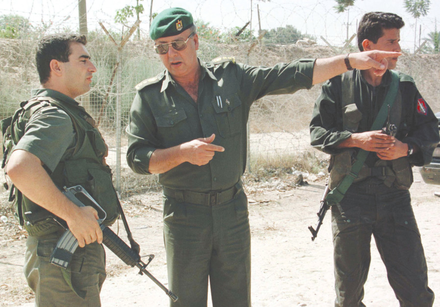 A PALESTINIAN POLICE officer gestures as he speaks with an IDF soldier during a joint patrol in 1998