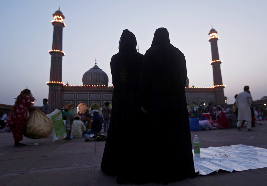 Muslim women stand as they pray after eating their iftar (breaking fast) meal during the holy month