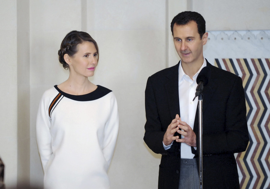 Syria's President Bashar al-Assad stands next to his wife Asma, as he addresses injured soldiers and