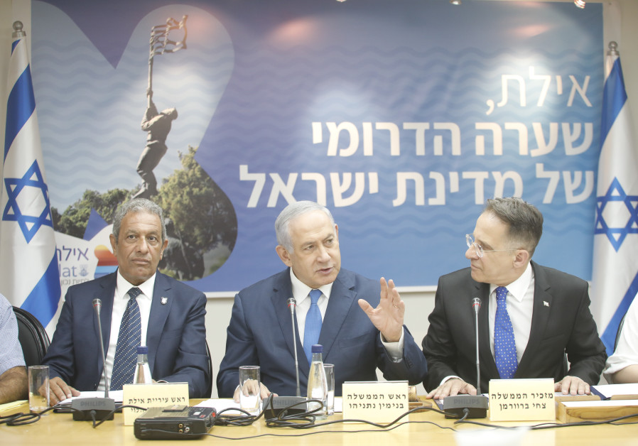 Prime Minister Benjamin Netanyahu (C) attends a cabinet meeting in Eilat, flanked by Cabinet Secreta