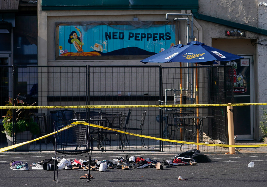 Shoes are piled in the rear of Ned Peppers Bar at the scene after a mass shooting in Dayton. (photo credit: REUTERS)
