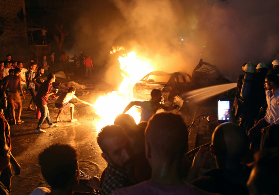 People extinguish a fire from a blast outside the National Cancer Institute, Cairo, Egypt August 4,