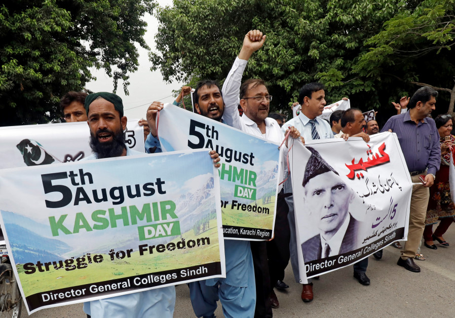 Demonstrators hold signs and chant slogans as they march in solidarity with the people of Kashmir, d