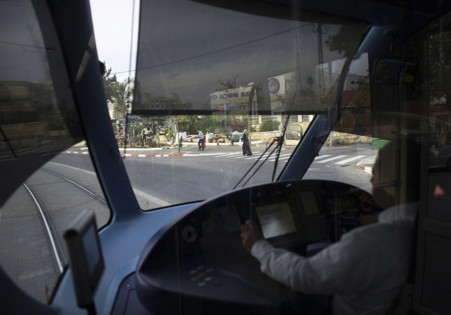 A light railway driver drives a tram in Jerusalem