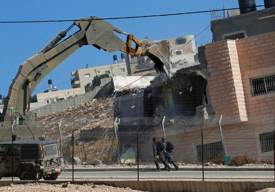 Israeli forces patrol as a machinery demolishes a Palestinian house in the village of Sur Baher whic