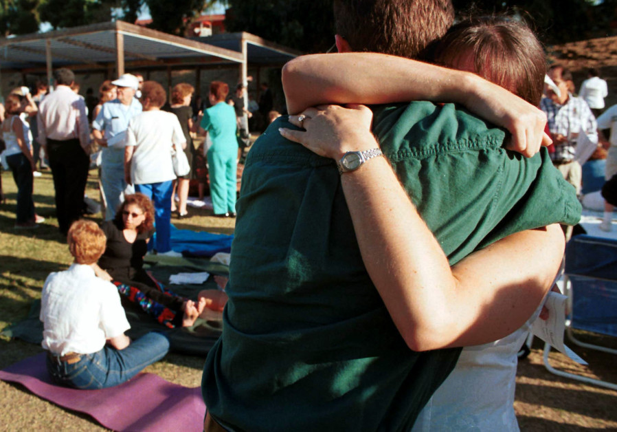 A couple embrace prior to a community gathering at the North Valley Jewish Community Center August 1