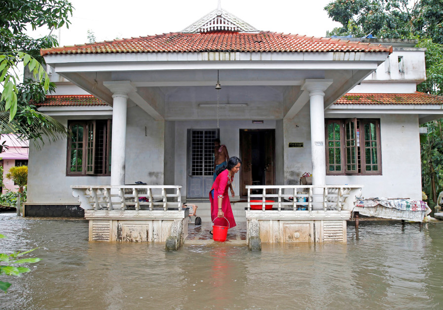 A woman clears out the water from her flooded house at Paravur on the outskirts of Kochi, in the sou