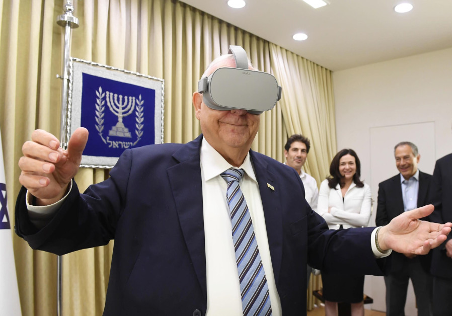 President Rivlin tries on virtual reality goggles at meeting with Sheryl Sandberg, 12 August 2019. (photo credit: Mark Neiman/GPO)