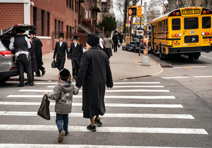 Pedestrians walk past a yeshiva in the South Williamsburg neighborhood of Brooklyn, April 9, 2019.