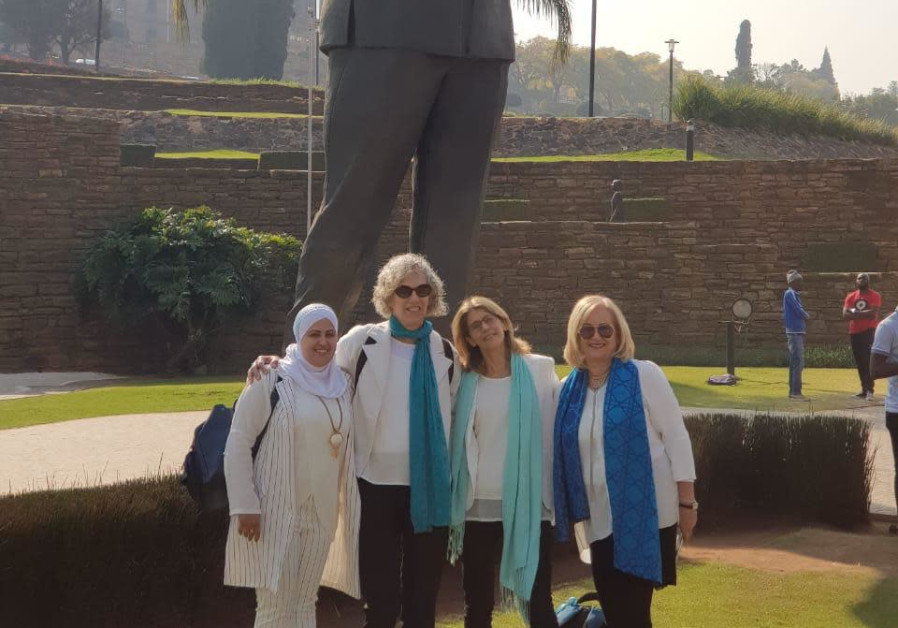 Four delegates from Women Wage Peace stand next to a statue of Nelson Mandela in South Africa