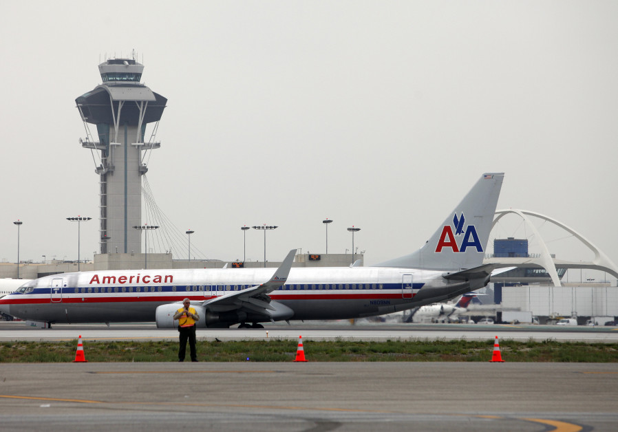An American Airlines jet passes the Air Traffic Control Tower on the runway at Los Angeles Internati