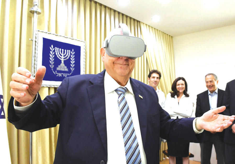 THE PRESIDENT tries on a set of virtual reality goggles given to him by Sheryl Sandberg. (MARK NEYMAN / GPO)