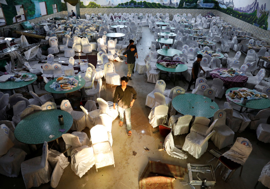 Workers inspect a damaged wedding hall after a blast in Kabul, Afghanistan August 18, 2019