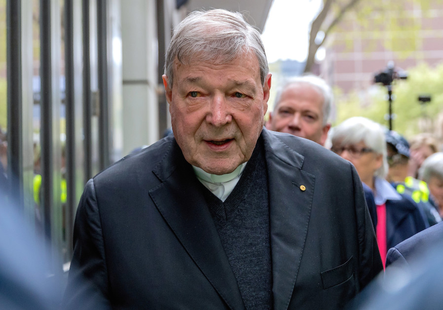 Vatican Treasurer Cardinal George Pell is surrounded by Australian police as he leaves the Melbourne