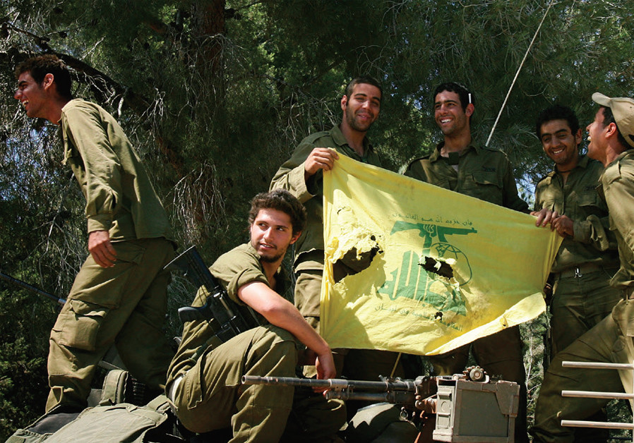 AN ISRAELI armoured personnel carrier (APC) team shows off a battle-torn Hezbollah flag after returning from fighting at the frontline inside Lebanon, near the Israeli village of Avivim on July 25, 2006. (Credit: RONEN ZVULUN / REUTERS)