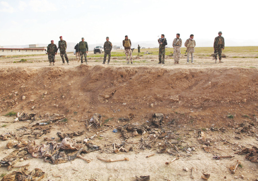 SYRIANS EXCAVATE a mass grave in Syria in the wake of the ISIS war