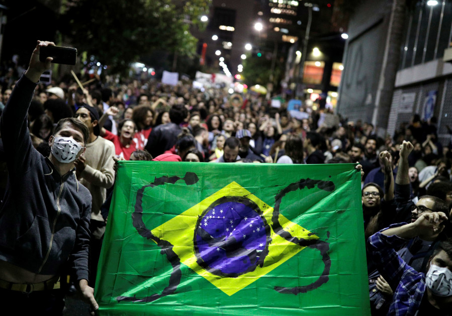 Protesters hold a Brazilian flag with the letters SOS written on it during a demonstration to demand for more protection for the Amazon rainforest, in Sao Paulo, Brazil, August 23, 2019 ( NACHOS DOCE / REUTERS)