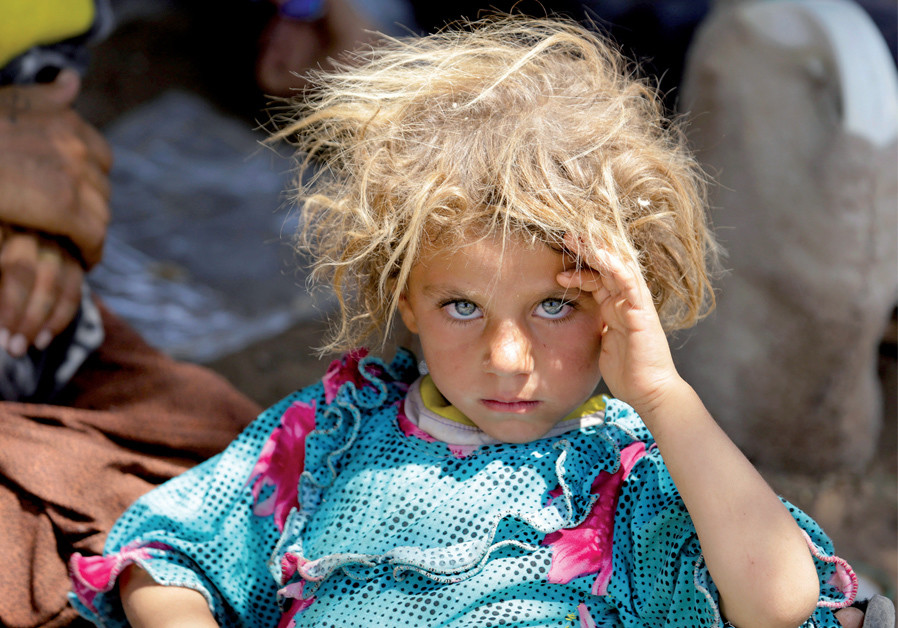A girl from the Yazidi sect fleeing the violence in Sinjar rests at the Iraqi-Syrian border crossing in Fishkhabour, Dohuk province, in 2014 ( Credit: YOUSSEF BOUDLAL / REUTERS)