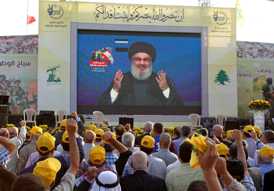 Lebanon's Hezbollah leader Sayyed Hassan Nasrallah gestures as he addresses his supporters via a scr