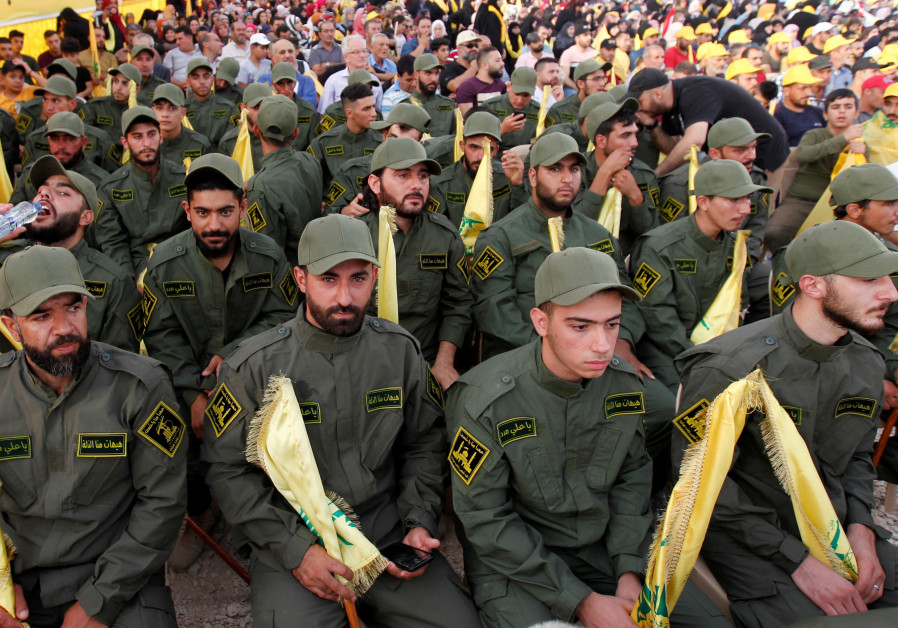 Lebanon's Hezbollah members hold party flags as they listen to their leader Sayyed Hassan Nasrallah