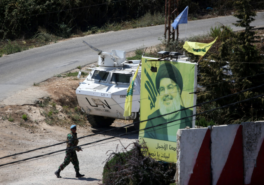 A U.N peacekeeper of the United Nations Interim Force in Lebanon (UNIFIL) walks near a poster depict