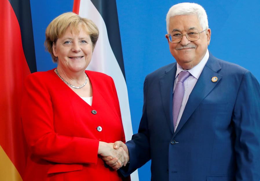 German Chancellor Angela Merkel and Palestinian President Mahmoud Abbas shake hands during a news co
