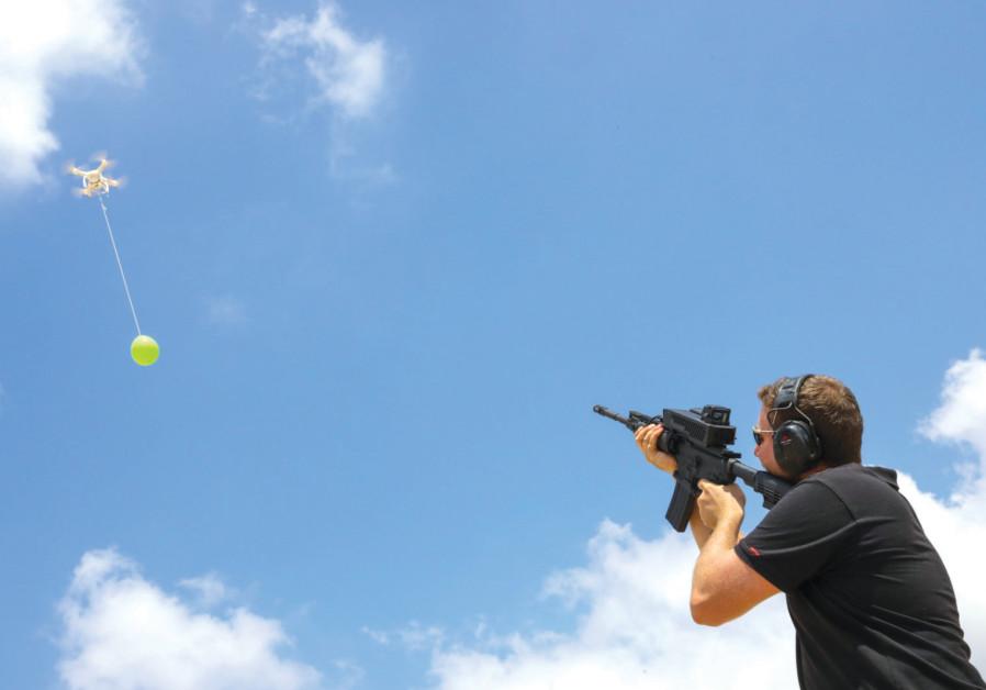 UN OPÉRATEUR montre comment SMASH agit contre un ballon comme ceux envoyés de Gaza en Israël.
