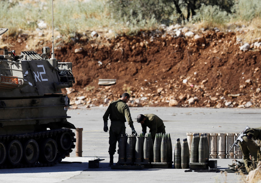Israeli soldiers stand next to shells and a mobile artillery unit near the Israeli side of the borde